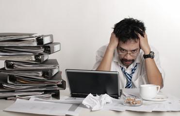 Ein Mann sitzt mit Stress im Büro