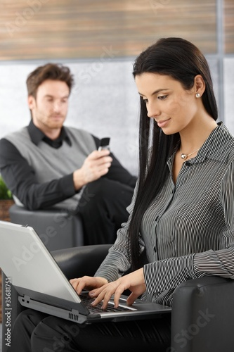 Attractive secretary working on laptop smiling