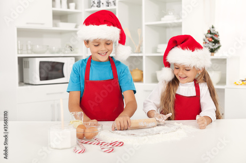 Happy christmas kids stretching the cookie dough