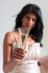 Junge exotische Frau prostet mit einem Sektglas
