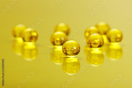 Macro of E vitamine capsules on yellow