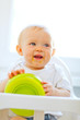 Eat smeared cheerful baby in baby chair playing with plate