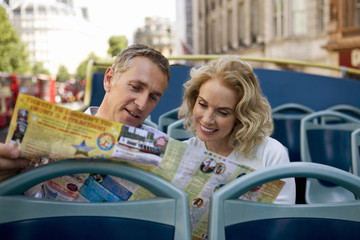 A middle-aged couple sitting on a bus, looking at a map