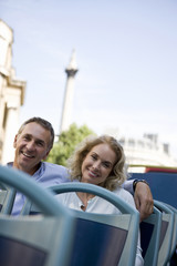A middle-aged couple sitting on a sightseeing bus, embracing