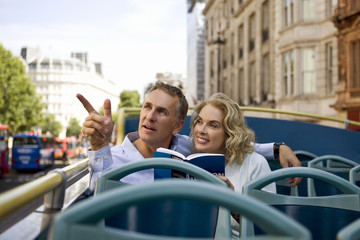 A couple sitting on a  bus, admiring the view