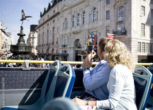 A middle-aged couple sitting on a bus, taking photographs