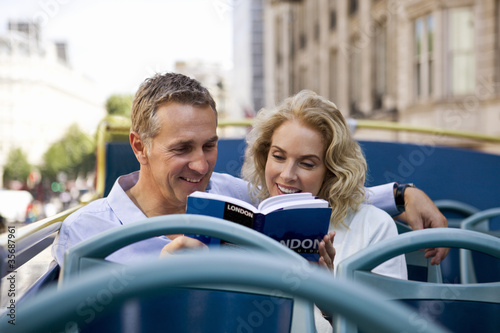 A middle-aged couple on a bus, looking at a guidebook