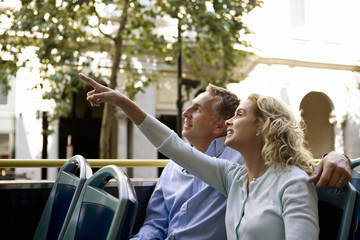 A couple sitting on a sightseeing bus, admiring the view