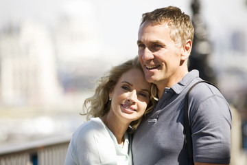 Portrait of a couple next to the river Thames embracing