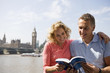 A couple standing near the Parliament, looking at a guidebook