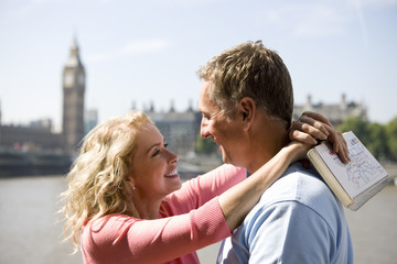 A couple standing near the Houses of Parliament, embracing