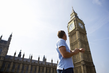 A man checking his watch next to Big Ben