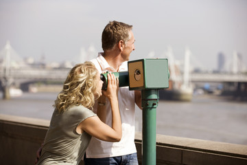 A middle-aged couple using a telescope