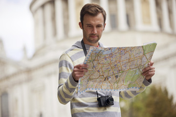 A man standing in front of St Paul's cathedral with a map
