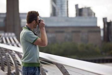 A man on the Millennium Bridge, taking a photograph