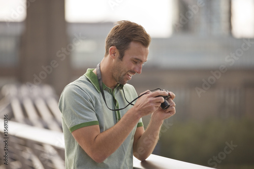 A  man looking at his photographs on his camera