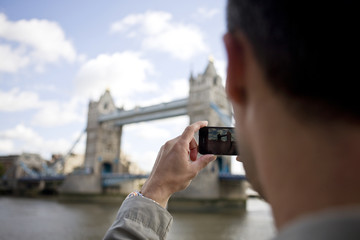 A mid-adult man taking a photograph of Tower Bridge