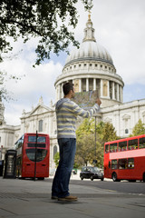 A man in front of St Paul's cathedral, looking at a map
