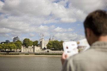 A man in front of the Tower of London, looking at a guidebook