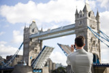 A man taking a photograph of Tower Bridge