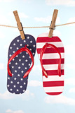 Flag patterned flip flop shoes hanging on clothes line