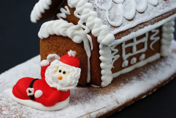 Santa Claus in front of gingerbread house.