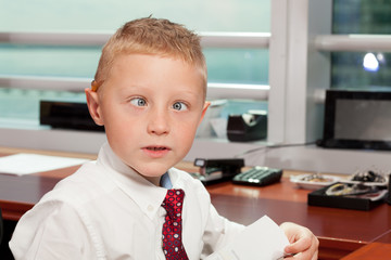 Cute boy with goofy face in business attire in an office