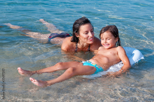Swimming lesson. Little girl and her mother swimming in the sea.