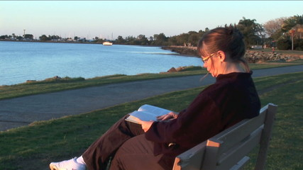 Woman reading a book at sunset at a quiet bay.