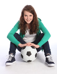 Teenage girl soccer player sits with football