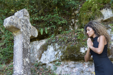 Prière devant une croix de pierre.