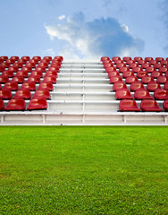 Red bleachers in the arena with green field and sky background