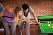 Young couple playing snooker