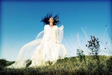 Portrait of romantic woman jumping on field