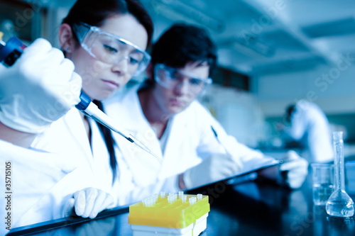 Cute scientist dropping liquid in test tubes while her partner i