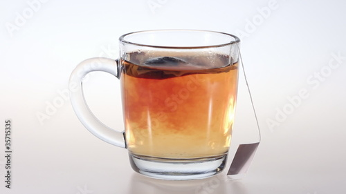 A tea bag in glass cup boiling water. Accelerated