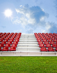 Red bleachers with green field and sky background