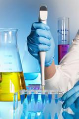 Cientifico depositando una muestra de liquido azul en unos tubos