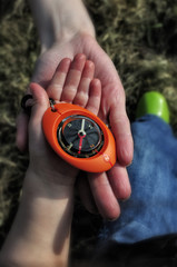 Compass in a child hand with mother supporting palm