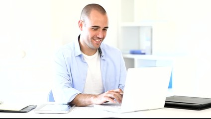 Handsome man at work typing on laptop computer