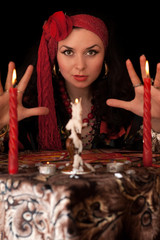 Witch at the table with candles. Isolated