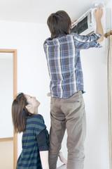 エアコンの点検をする男性と手伝う女性