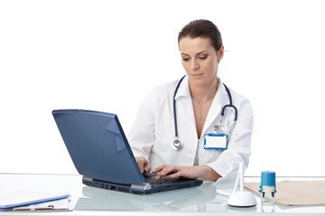 General practitioner typing on computer