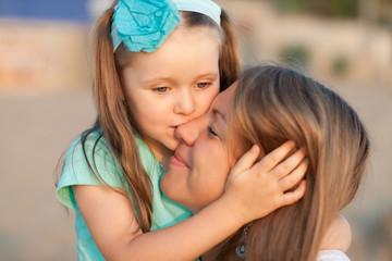 Красивый  маленький ребенок целует свою маму.