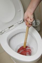 homme débouchant WC avec ventouse