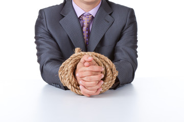 Business men at the desk tied hands with rope