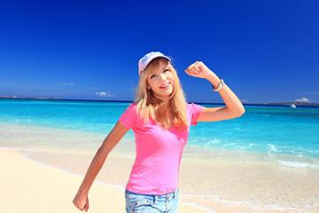 波打ち際をウォーキングする笑顔の女性