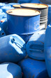Old colored oil barrels and blue canisters