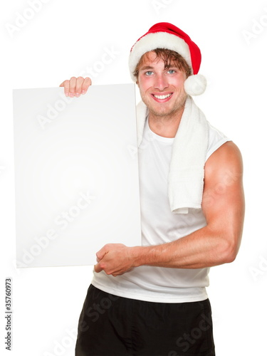 Fitness man holding sign wearing christmas santa hat