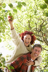 Couple picking apples off tree